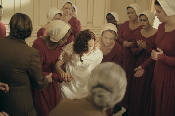 "The Handmaid's Tale -- ""Birth Day"" -- Episode 102 -- Offred and her fellow Handmaids assist with the delivery of Janine's baby, prompting Offred to recall her own daughter's birth. Offred draws closer to Ofglen while dreading a secret meeting with the Commander. Janine (Madeline Brewer), center and Offred (Elisabeth Moss), shown. (Photo by: George Kraychyk/Hulu)"