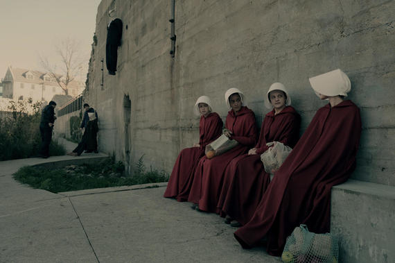 "The Handmaid's Tale -- ""Birth Day"" -- Episode 102 -- Offred and her fellow Handmaids assist with the delivery of Janine's baby, prompting Offred to recall her own daughter's birth. Offred draws closer to Ofglen while dreading a secret meeting with the Commander. Offred (Elisabeth Moss), second from right, shown. (Photo by: George Kraychyk/Hulu)"