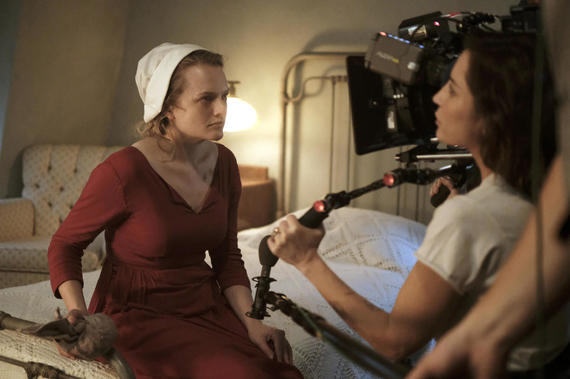 "The Handmaid's Tale -- ""Late"" Episode 103 -- Offred visits Janine's baby with Serena Joy and remembers the early days of the revolution before Gilead. Ofglen faces a difficult challenge. Behind the scenes with Offred (Elisabeth Moss) and Reed Morano, shown. (Photo by: George Kraychyk/Hulu)"