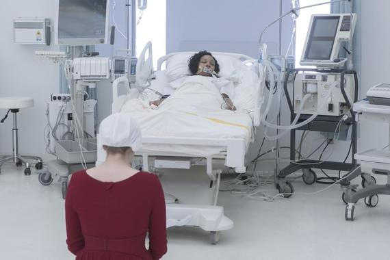 "The Handmaid's Tale -- ""Heroic"" - Episode 309 -- Confined in a hospital, June's sanity begins to fray. An encounter with Serena Joy forces June to reassess her recent actions. June (Elisabeth Moss) and Ofmatthew (Ashleigh LaThrop), shown. (Photo by: Sophie Giraud/Hulu)"