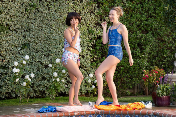 "PEN15 -- ""Pool"" - Episode 201 -- Two days after the dance, Maya and Anna reluctantly go to a lame pool party. A crush unexpectedly shows up, causing them to question their sanity and reputations. Maya Ishii-Peters (Maya Erskine) and Anna Kone (Anna Konkle), shown. (Photo by: Erica Parise/Hulu)"