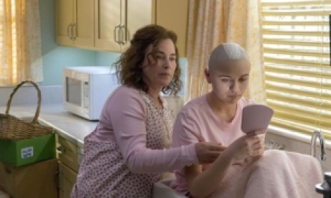 Woman with a young girl shaving her head in a sink