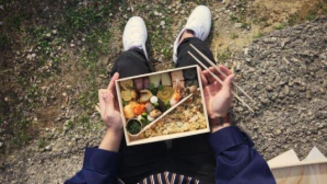 man holding box of sushi and chopsticks outside