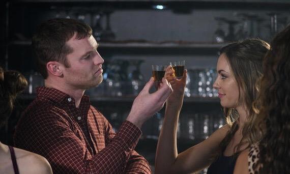Man and woman taking shots at a bar