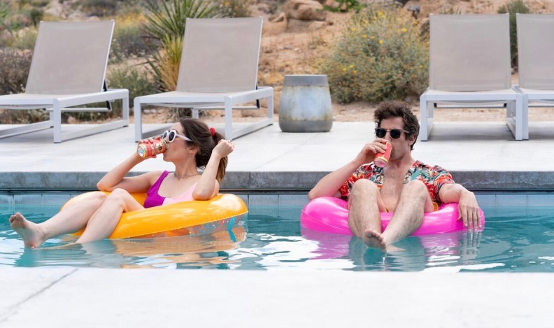 Man and woman sitting on pool floats drinking from cans