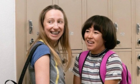 Teenage girls with braces at their lockers smiling