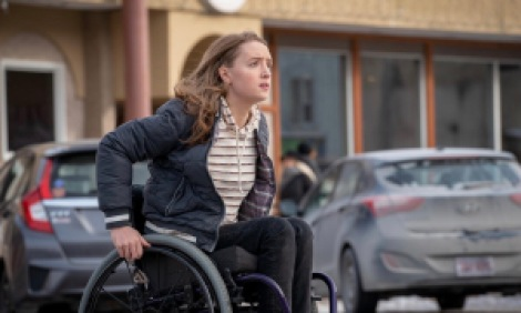 Teenage girl in a wheelchair fleeing a parking lot