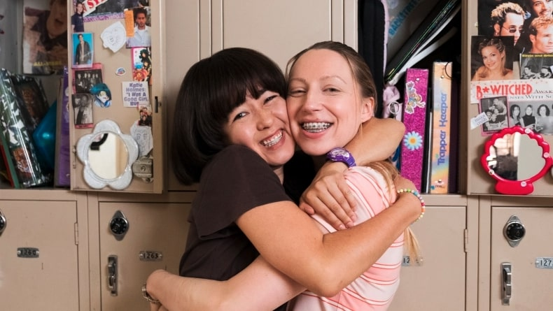 Best friends hugging and smiling at their locker.