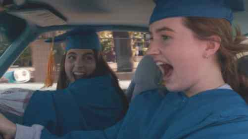 High School girls wearing caps and gowns driving in the car