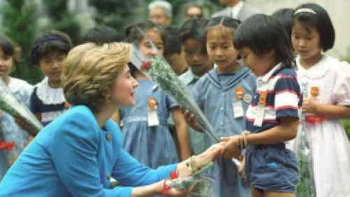 Hillary Clinton kneeling down shaking a young boy's hand