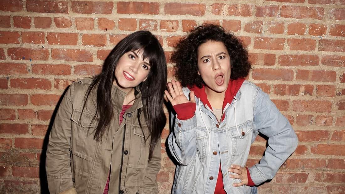 Comedians Abbi Jacobson and Ilana Glazer posing against a brick wall