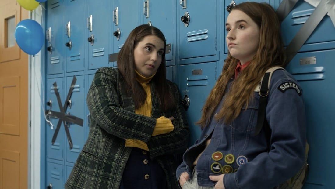 Beanie Feldstein and Kaitlyn Dever standing against blue lockers in the movie Booksmart.