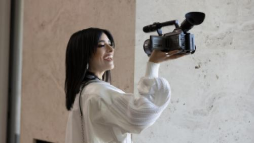 Dixie D'Amelio holding a video camera.